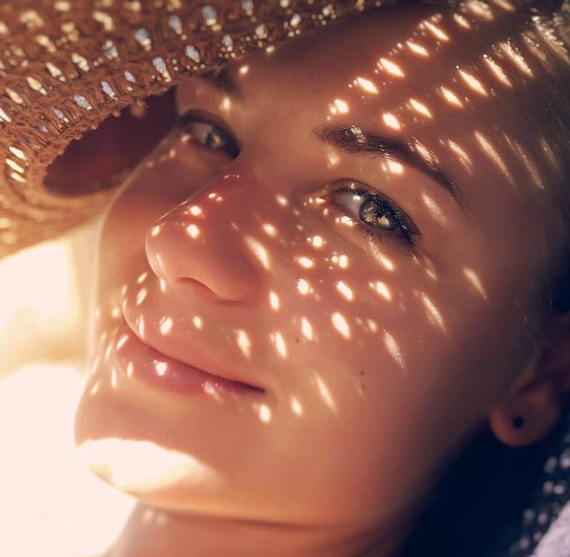 Closeup of smiling young woman holding a hat to shield brilliant sunshine