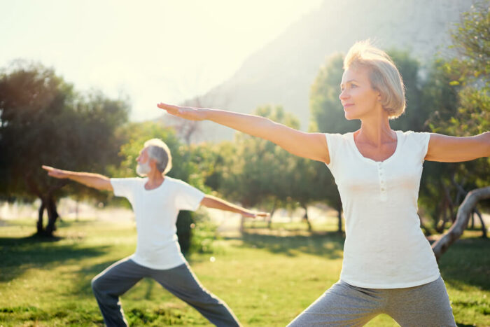 Older man and woman doing yoga ouside