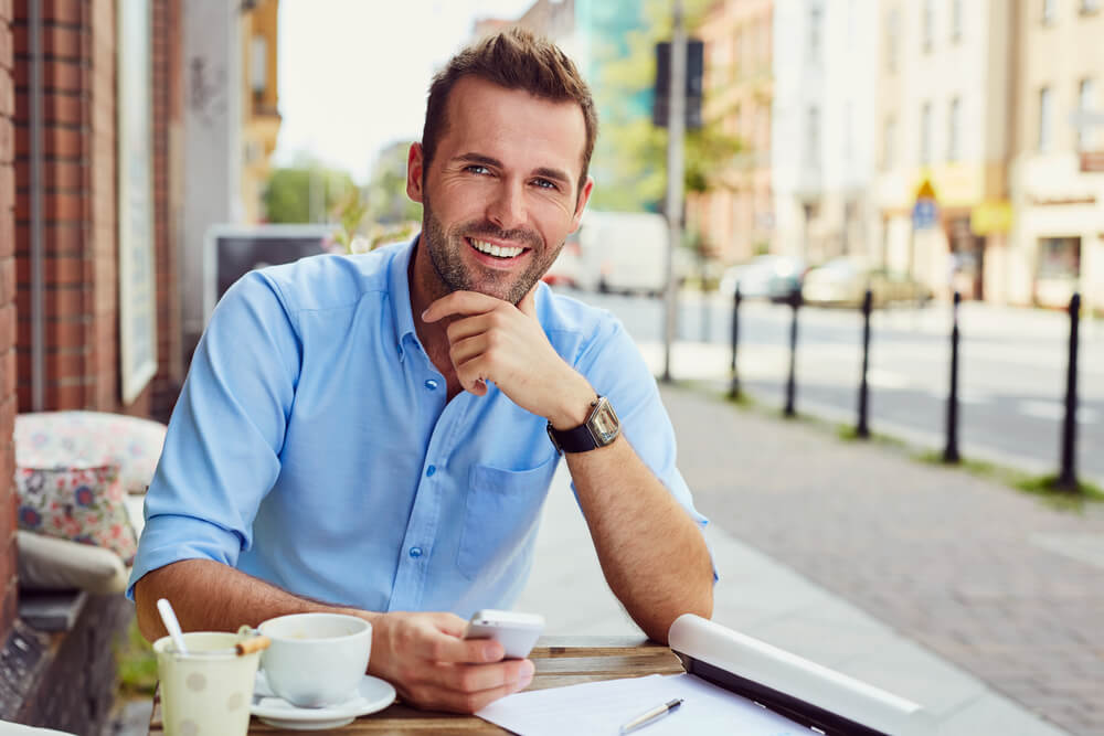 Smiling young professional man working outside of a restaurant