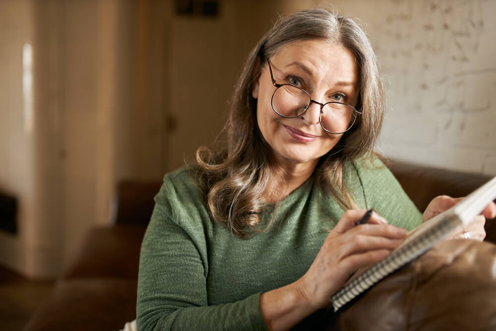 Older woman with large reading glasses writing in a notebook