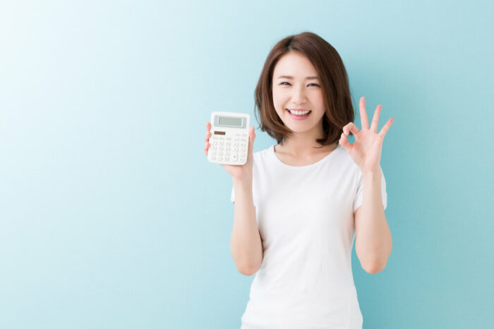 Smiling young holding a calculator. Light green backgound.