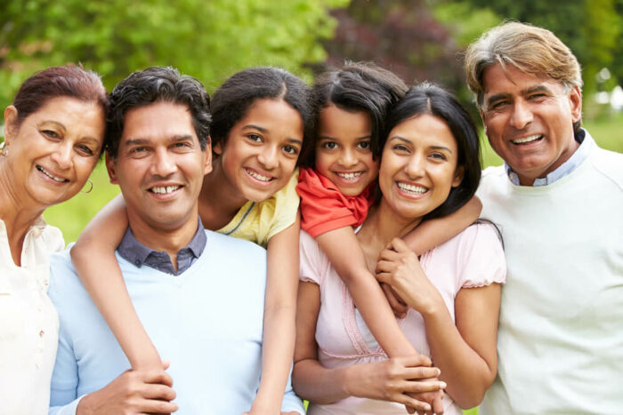 Smiling family with 2 young children and grandparents