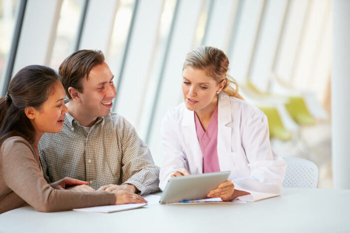 Smiling man and woman looking at a digital device in a doctors office